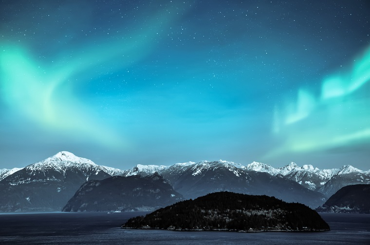 northern lights over snow mountains