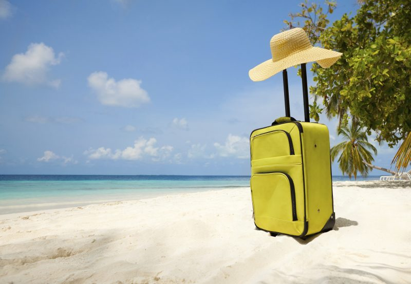 Suitcase and big straw hat on a beautiful beach