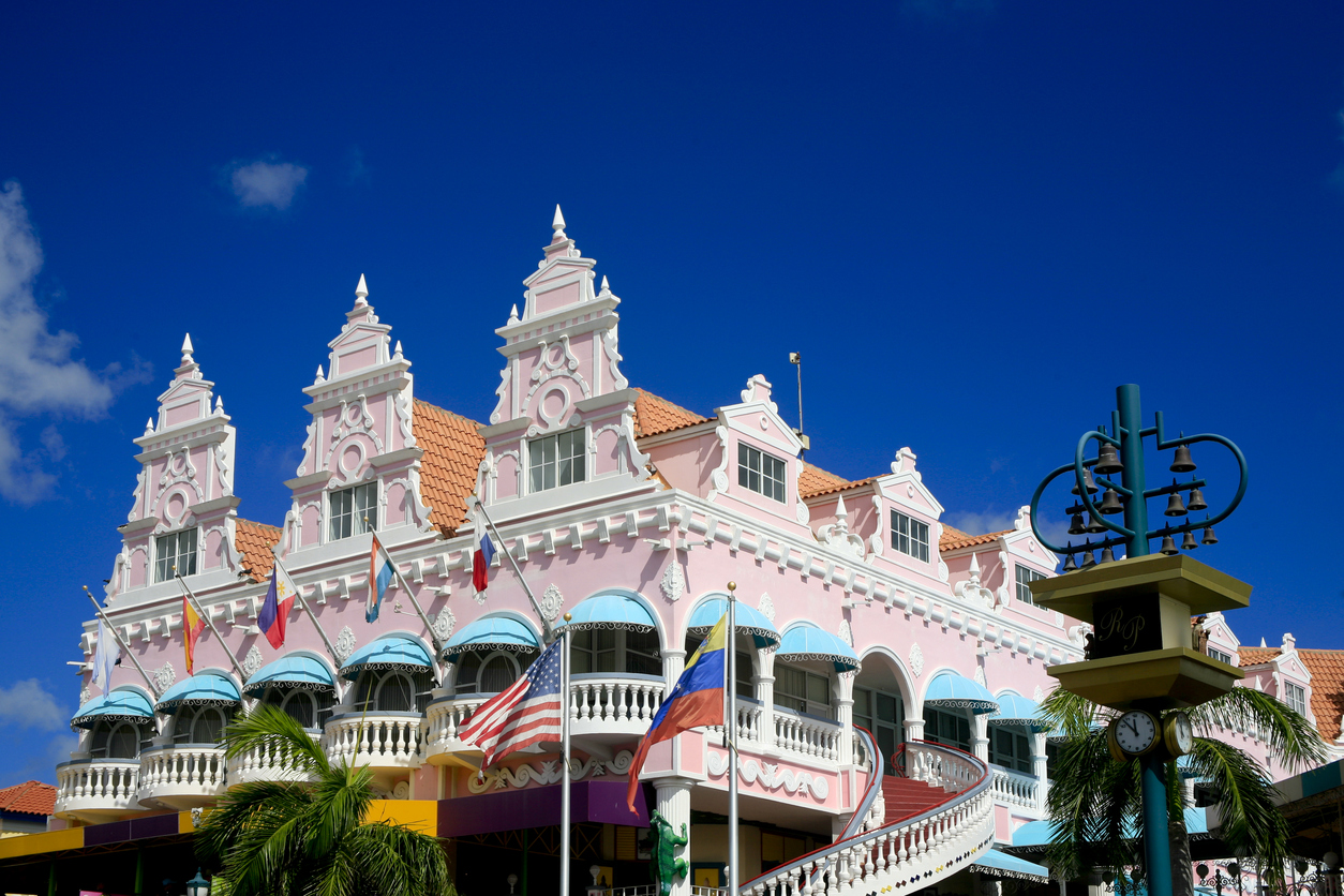 The pink iconic Royal Plaza, Oranjestad, Aruba with the bell tower on the right. An outdoor staircase leads onto the second floor. Deep blue sky.