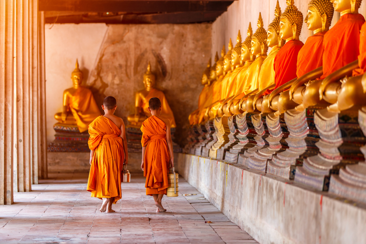 Two novices walking return and talking in old temple