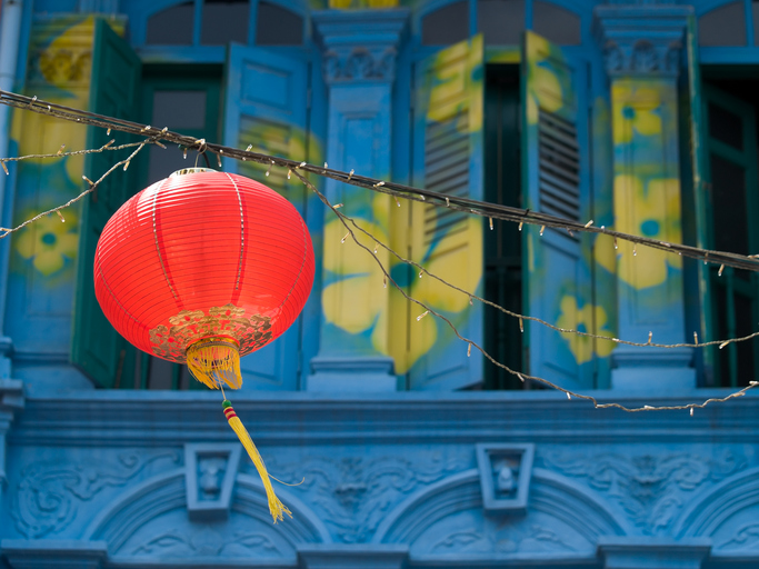 Hanging Red Lantern over Street in Chinatown against a blue facade painted with yellow flowers