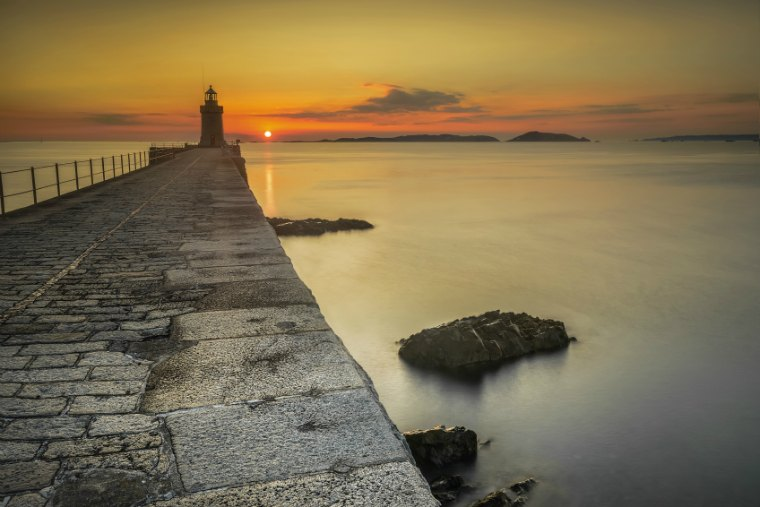 The sunrises over herm, taken from castle cornet break water, St Peter Port, Guernsey Channel Islands