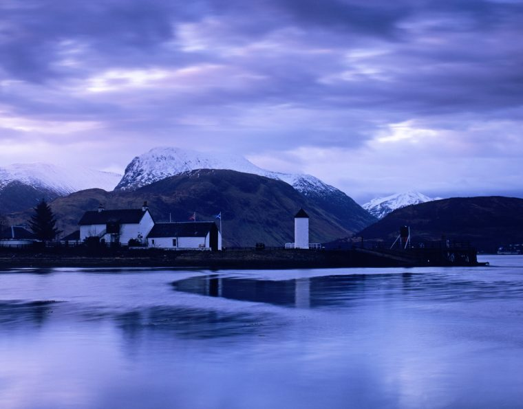 The quayside and cottages at Corpach, near Fort William, Argyll, at daybreak. shot in February, with snow on the mountains behind